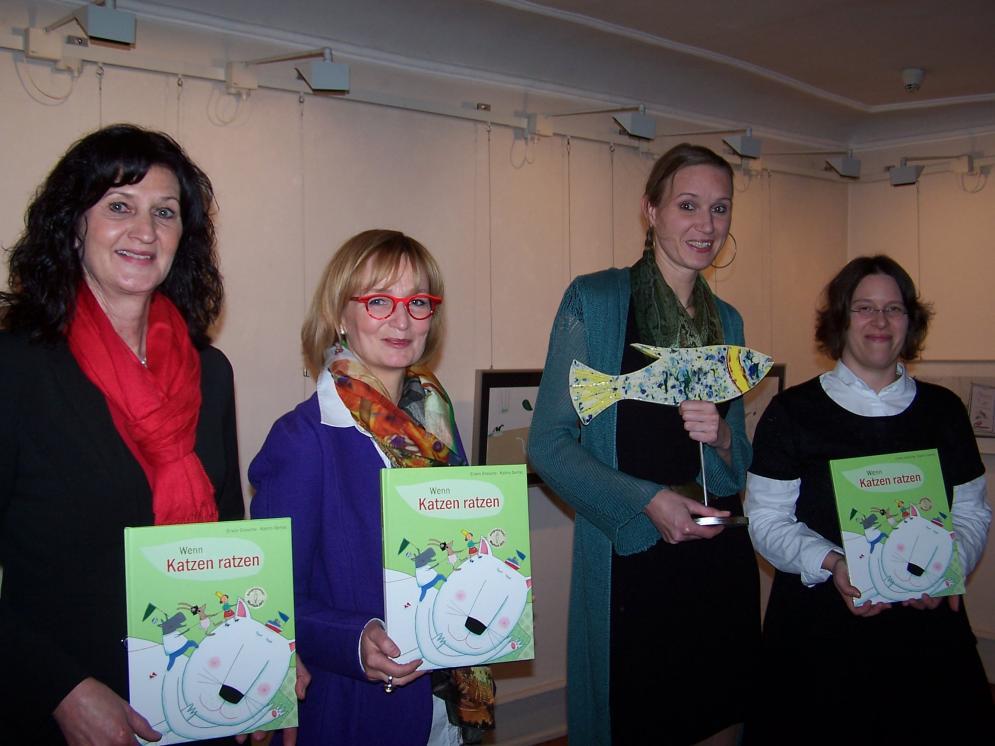 Erste Bürgermeisterin Helga Schmidt-Neder (v.li.), Programmleiterin Arena-Verlag Isa-Maria Röhrig-Roth und Rebecca Schmalz (Lektorin Arena) gratulieren Katrin Oertel (Zweite von rechts).